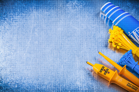 cable tie: Yellow electrical tester cable ties blue construction plans on metallic background electricity concept.