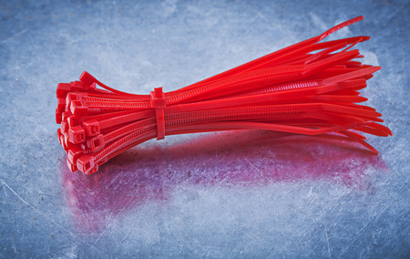 cable tie: Red plastic self-locking cable ties on metallic background construction concept.