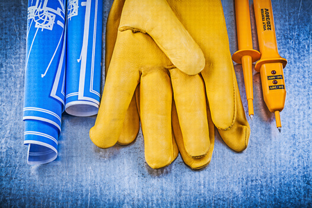 protective gloves: Yellow electrical tester protective gloves blue rolled construction plans on metallic background.