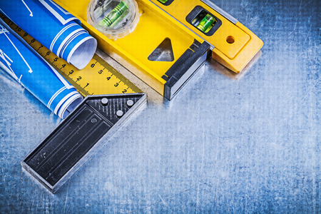 square ruler: Blue engineering drawings construction levels square ruler on metallic background. Stock Photo