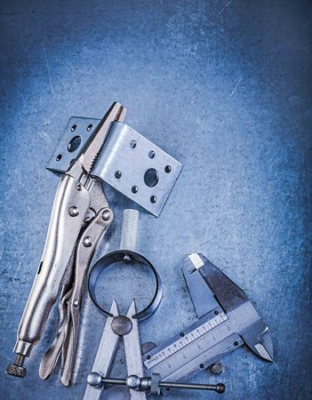 mounting: Metal lock jaw pliers slide caliper perforated mounting brackets construction drawing compass on metallic background.