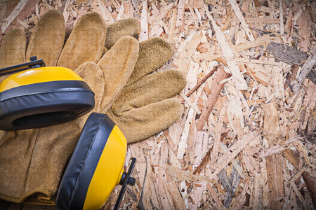 chipboard: Safety leather gloves earmuffs on chipboard.