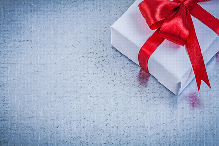 Giftbox with red bow on metallic background holidays concept.