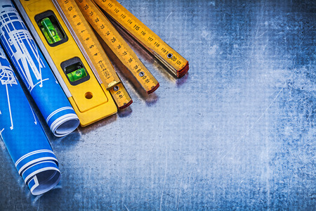 construction level: Blue rolled blueprints wooden meter construction level on metallic background.
