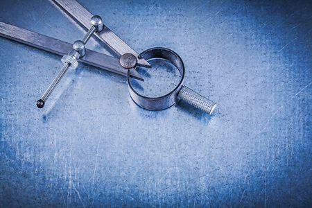 compas de dibujo: Construcción metálica dibujo brújula en el fondo metálico directamente encima.