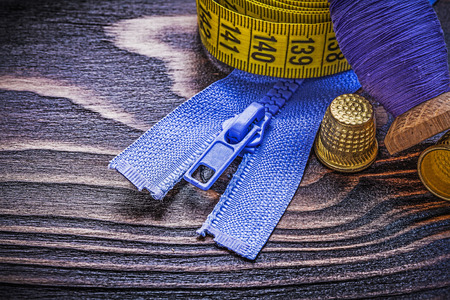 fastener: Vintage spool of thread measuring tape thimbles zip fastener on wooden board needlework concept.