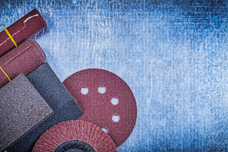 emery paper: Assortment of abrasive equipment on scratched metallic background.