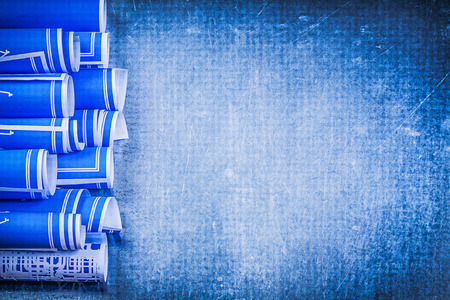 blue metallic background: Blue rolled construction drawings on metallic background maintenance concept.