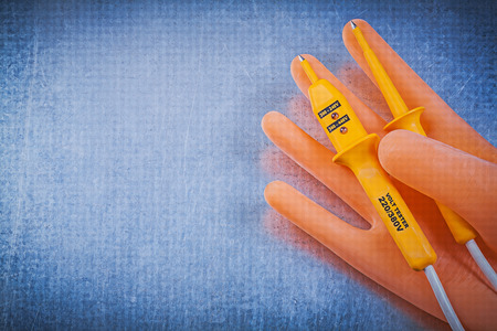dielectric: Dielectric rubber gloves electric tester on metallic background electricity concept.