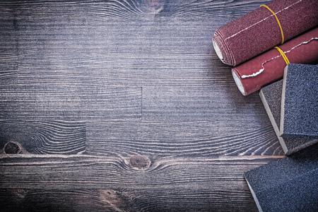 emery paper: Rolled abrasive paper sponges on vintage wood board copy space.