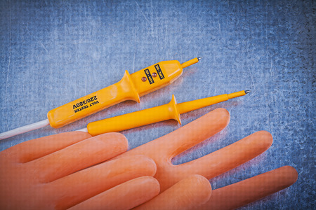 the tester: Electricians rubber gloves electric tester on metallic background electricity concept.