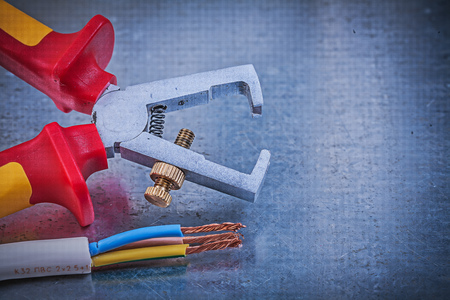 cable cutter: Insulated strippers electrical wires on metallic background directly above electricity concept. Stock Photo