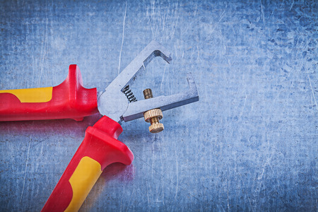 insulated: Insulated wire strippers on metallic background electricity concept.