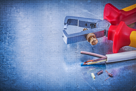 cable cutter: Insulated strippers electric wires on metallic background electricity concept.
