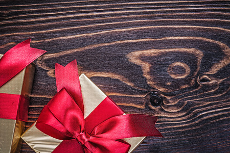 christmas present box: Boxes with red present ribbons on wood board horizontal version.
