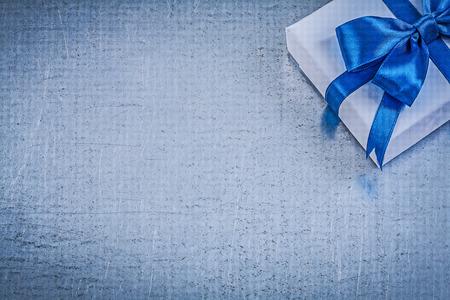 blue metallic background: Present box blue bow on metallic background copyspace celebrations concept.