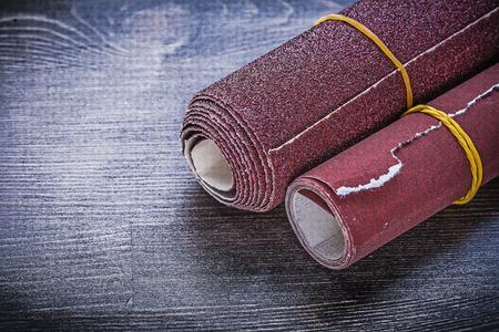 abrasive: Rolled sandpaper on vintage wooden board abrasive materials. Stock Photo
