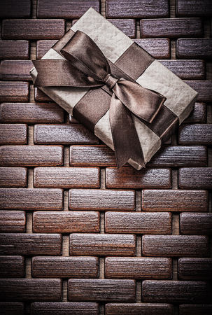 matting: Packed present with ribbon on wooden wicker matting holidays concept. Stock Photo