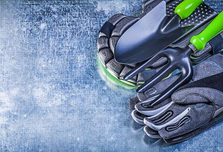 protectors: Gardening protective gloves knee protectors hand shovel trowel fork on metallic background agriculture concept.