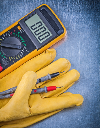 dielectric: Digital electrical tester protective gloves on metallic background electricity concept.