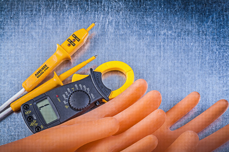 dielectric: Digital ammeter electric tester dielectric rubber gloves on metallic background electricity concept.