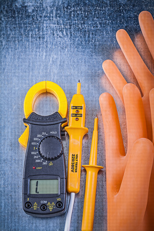 dielectric: Digital ammeter electric tester electricians rubber gloves on metallic background electricity concept.