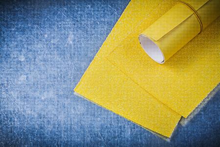 emery paper: Yellow emery paper on metallic background abrasive tools.