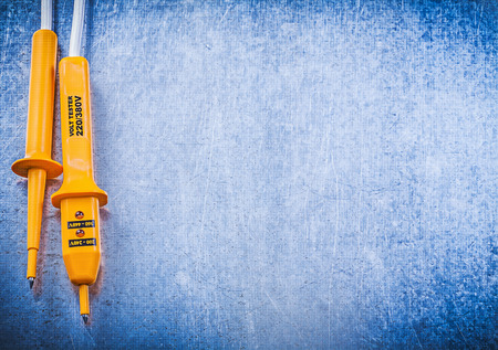 dielectric: Yellow electrical tester on scratched metallic background electricity concept.