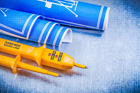 dielectric: Yellow electrical tester blue engineering drawings on metallic background electricity concept.