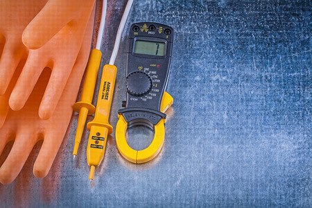 the tester: Digital clamp meter electrical tester insulating rubber gloves on metallic background.