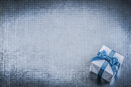 giftbox: Giftbox blue bow on metallic background greeting card holidays concept.