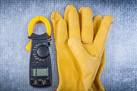 ammeter: Digital ammeter safety gloves on metallic background.