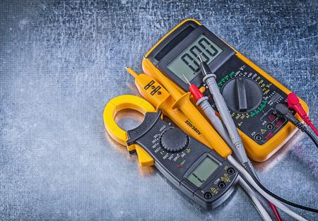 Digital clamp meter electric tester multimeter on metallic background.