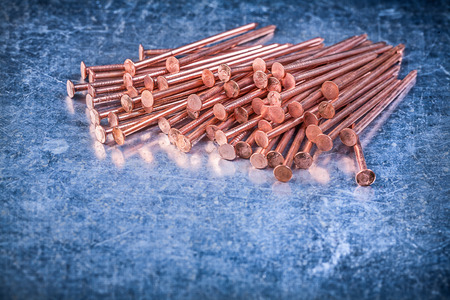 construction nails: Heap of copper construction nails on metallic background. Stock Photo