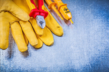 dielectric: Yellow electrical tester safety gloves sharp cutting pliers on metallic background electricity concept.