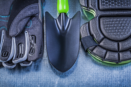 protectors: Gardening safety gloves knee protectors hand shovel on metallic background agriculture concept. Stock Photo