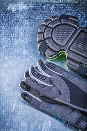 protective: Gardening protective gloves knee pads on metallic background agriculture concept.
