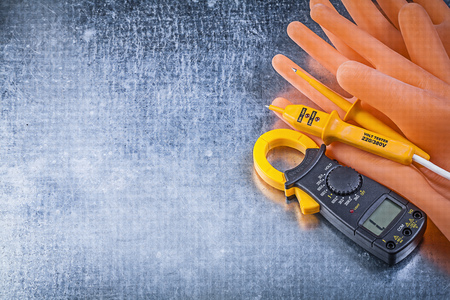 the tester: Digital clamp meter electrical tester insulating gloves on metallic background electricity concept.