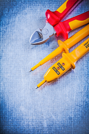 wire cutter: Yellow electrical tester red sharp wire cutter on metallic background electricity concept.
