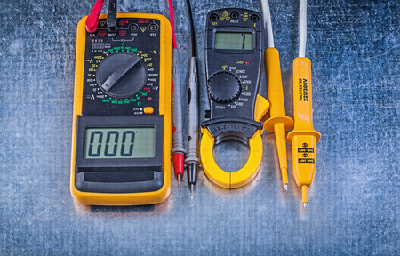 dielectric: Set of digital clamp meter electric tester multimeter on metallic background electricity concept.