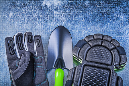knee pads: Gardening safety gloves knee pads hand shovel on metallic background agriculture concept. Stock Photo