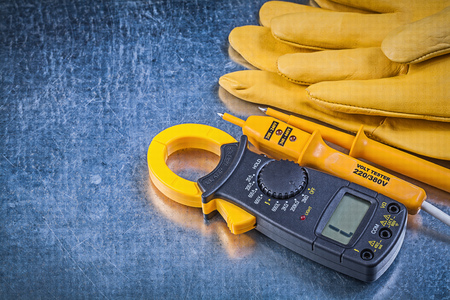 dielectric: Digital clamp meter electric tester protective gloves on scratched metallic background electricity concept.