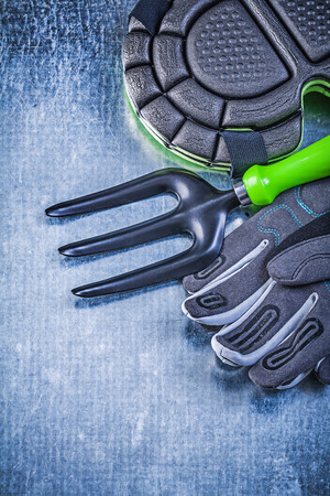 knee pads: Gardening protective gloves knee pads trowel fork on metallic background agriculture concept. Stock Photo
