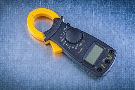 dielectric: Digital clamp meter on metallic background.