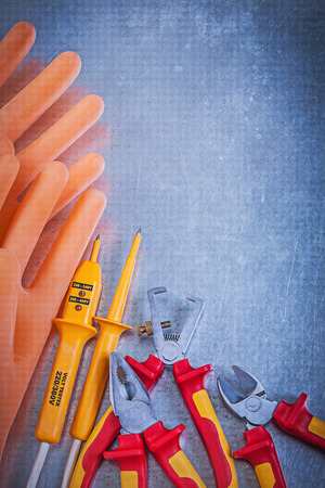wire cutter: Insulating rubber gloves insulated wire strippers electrical tester pliers wire cutter on metallic background. Stock Photo