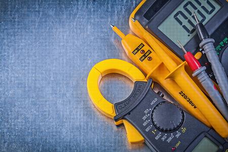 the tester: Digital clamp meter electrical tester multimeter on metallic background.