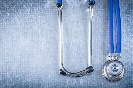 auscultoscope: Ausculator diagnostic tool on scratched metallic background top view medicine concept.