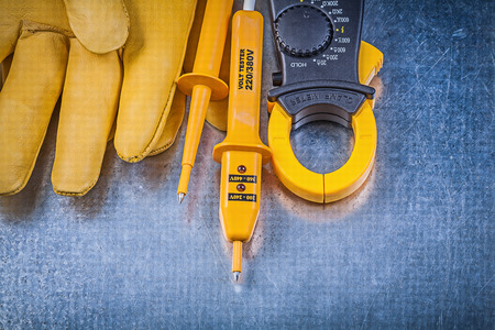 dielectric: Digital amperemeter electrical tester safety gloves on metallic surface electricity concept. Stock Photo