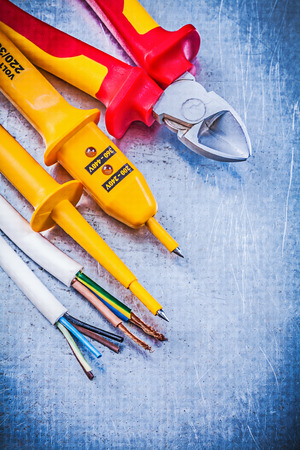 cable cutter: Yellow electrical tester wires cutting pliers on metallic background electricity concept.