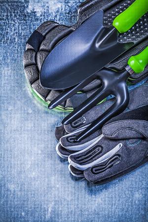 protectors: Gardening safety gloves knee protectors hand shovel trowel fork on metallic background agriculture concept.